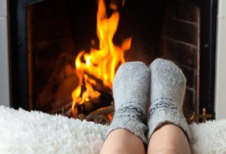 Calentando pies con el fuego de un hogar de leña