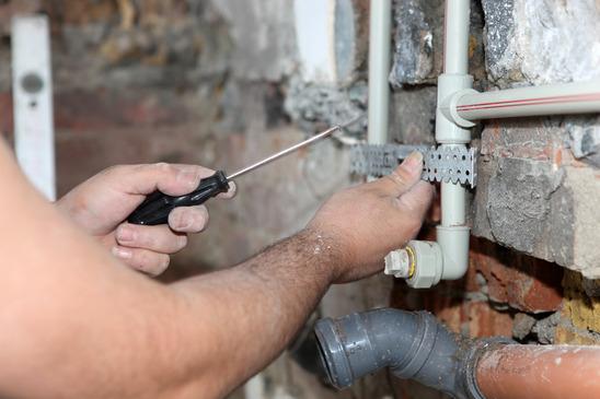 Especialista en fontanería trabajando en una reforma de cocina